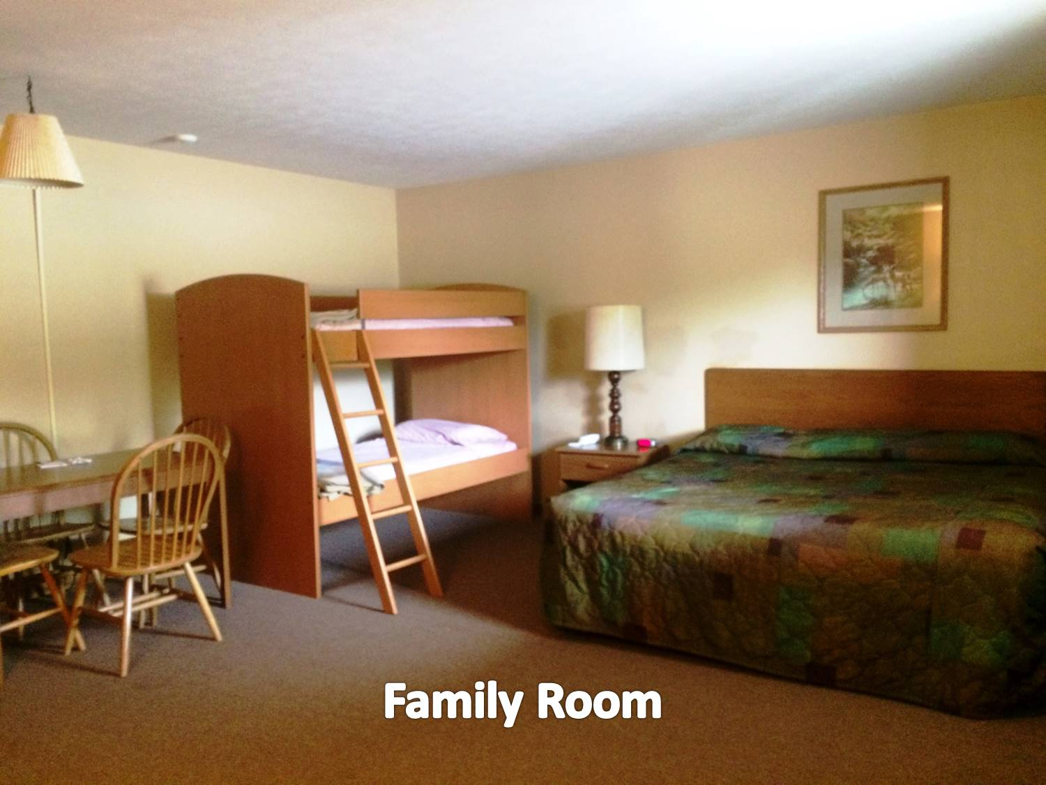 Room with one king bed, a set of bunk beds, plus a pullout sofa, and appropriate furnishings.